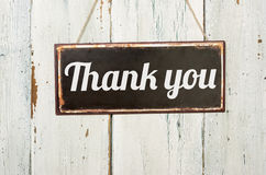 Thank you. Old metal sign in front of a white wooden wall - Thank you Royalty Free Stock Photography