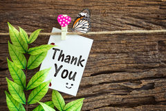 Thank you paper note hanging by red heart clips on wooden background stock photo