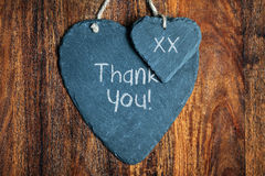 Thank you sign. Thank you note written in chalk on a slate heart hanging on a wooden background Stock Images