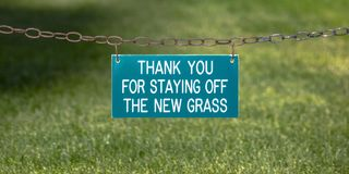 Thank you sign on a chain over a grassy lawn. Thank you for staying off the new grass printed on a green sign board. The sign is hanging on a rusty chain over royalty free stock photography