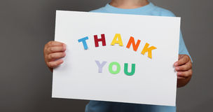 Thank You sign in children's hands. Letters cut from paper and pasted on sheet stock photography