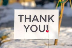 Thank You sign isolated against blurred background. Close up of a Thank You sign isolated against a blurred background. The sign is printed on white surface stock photography