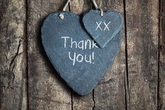 Thank you sign. Thank you note written in chalk on a slate heart hanging on a wooden background Stock Photo