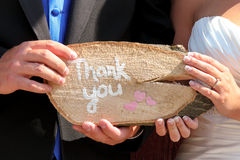 Thank you sign at wedding. A newly married couple holding a handmade thank you sign Royalty Free Stock Photos