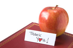 Thank You Teacher!. A red apple for the teacher resting on a hardback book. Isolated on white with a hand written Thank You (Heart) message card. Copy space Stock Image