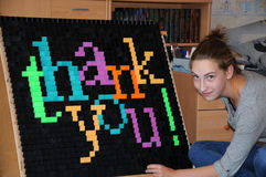 Thank you. Teenager girl builds the words thank you at the fall wall with domino blocs Royalty Free Stock Photography