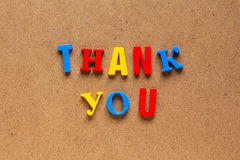 Thank you text on cardboard background. Thank you phrase written by plastic colorful letters on cardboard background stock images