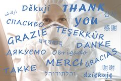 Thank you text on different world global languages with tired female nurse doctor or medical worker in ppe facemask on