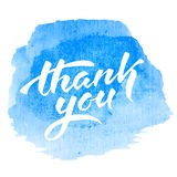 Thank you text. Vector handwritten calligraphy inscription on blue grunge watercolor stain background - Thank you. Isolated on white background Royalty Free Stock Photo