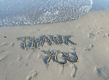 THANK YOU text written on the sand of the beach