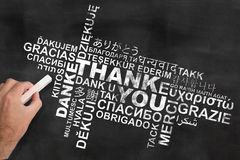 Thank you in various languages on blackboard. Hand holding a piece of chalk writing thank you in different languages on blackboard chalkboard royalty free stock photos