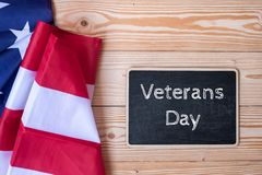 Thank You Veterans text written in chalkboard with flag of the United States of America on wooden background. stock image