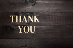 Thank you. Wooden letters forming words THANK YOU written on black wooden background stock photo