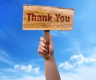 Thank you wooden sign. A woman holding thank you wooden sign on blue sky background stock photo