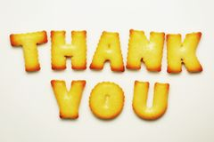 Thank you word from alphabet biscuits on white background stock images