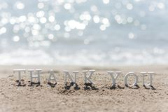 Thank you word drawn on the beach sand royalty free stock images