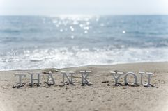 Thank you word drawn on the beach sand stock photo