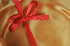 Thank you word on red ribbon. On yellow fabric background Royalty Free Stock Image