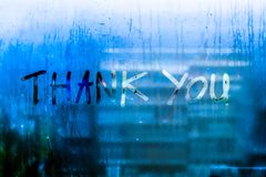 Thank you words rain drops water drops written wrie on window glass blue tone blur nature bokeh background royalty free stock photography