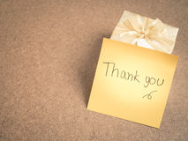 Thank you words on sticky note with gold gift box on wood backgr Stock Photos