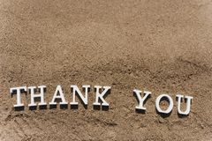 Thank you word drawn on the beach sand stock image
