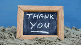 Thank you. Written on a chalkboard at the beach Royalty Free Stock Photo