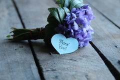 Thank you, written on heart. Thank you written on tag and a bouquet of violets Stock Image