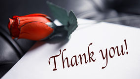 Thank You written on paper next to red rose. The words Thank You written on paper next to red rose on black leather Royalty Free Stock Photography