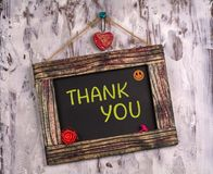 Thank you written on Vintage sign board. Thank you written on Vintage wooden sign board hanging on color white wood with heart and flower and smile face emoji royalty free stock photography
