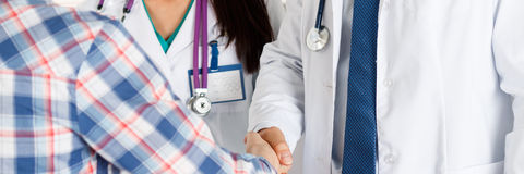 Thankful handclasp for excellent treatment. Male doctor shaking hands with female patient letterbox view. Partnership, trust and medical ethics concept Stock Image