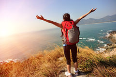 Thankful hiking woman seaside mountain. Thankful hiking young asian woman open arms at seaside mountain peak Royalty Free Stock Photo