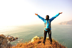 Thankful hiking woman seaside. Thankful hiking young asian woman open arms at seaside Royalty Free Stock Photography