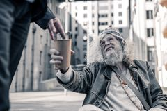 Distressed long-haired man being poor homeless and collecting money. Thankful homeless man. Distressed long-haired men being poor homeless and collecting money royalty free stock images