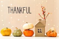 Thankful message with pumpkins with a house. Thankful message with collection of autumn pumpkins with a toy house royalty free stock images
