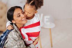 Thankful mother receiving a kiss from her child. Grateful for this. Stunning brave pretty women being welcomed with love after working some weeks away from home stock photos