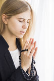 Thankful pray. Young female prayer with rosary Royalty Free Stock Image
