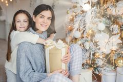 Thankful small female child embraces her mother who gave present, spend wonderful unforgettable time together, celebrate Christmas. Brunette women and daughter royalty free stock images