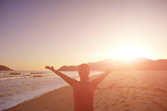 Thankful woman open arms on beach. Woman open arms on beach under sunset Stock Photos