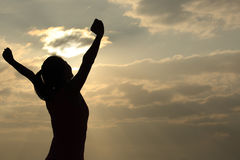 Thankful woman open arms to the sunrise Stock Image