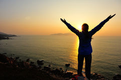 Thankful woman open arms to the sunrise. Stand at seaside mountain Stock Photography