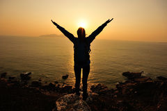 Thankful woman open arms to the sunrise. Stand at seaside mountain Stock Image
