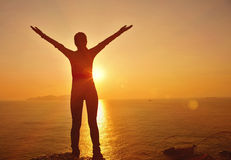 Thankful woman open arms to the sunrise. Stand at seaside mountain Stock Photo