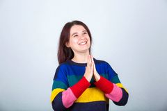 Namaste gesture. Thankful young woman smiling and holding hands like praying. Positive casual girl making namaste gesture. Happy human emotion over grey stock image