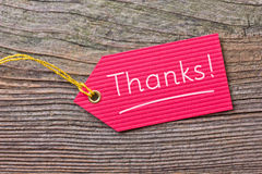 Thanks. Red label and lettering thanks on wooden ground royalty free stock photos