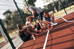 Thanks for game. Group of young men in sports clothing smiling while sitting on the basketball field outdoors royalty free stock photos