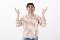 Thanks god it is friday. Portrait of grateful successful male teacher in striped shirt, raising hands and looking up stock photography
