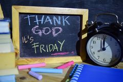 Thanks god it`s friday on phrase colorful handwritten on blackboard. Education and business concept. Alarm clock, chalk, books on black background royalty free stock image
