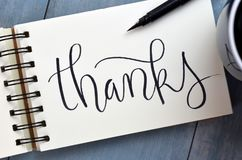 THANKS hand-lettered in notepad. THANKS hand-lettered in notebook on blue wooden desk with pen and cup of coffee royalty free stock photos