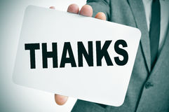 Thanks. A man wearing a suit showing a signboard with the word thanks written in it Royalty Free Stock Images