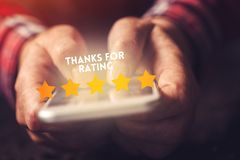 Thanks for rating message on smartphone screen. In female hand. Customer service survey feedback concept stock images